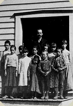 a teacher and students outside the little red schoolhouse