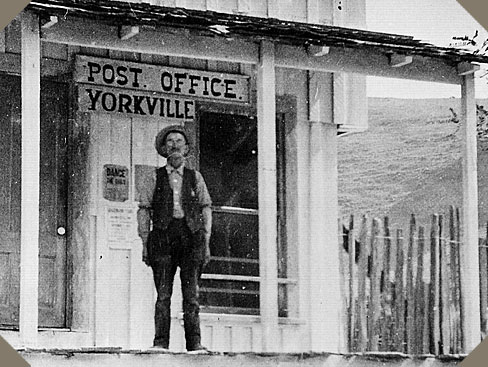 a man with a bushy mustache stands on the porch of Yorkville Post Office, 1800s